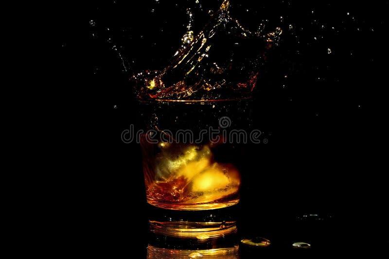 De plons van de whisky in een glas stock afbeelding