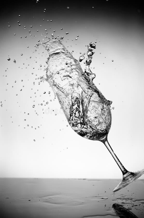 De plons van het glas en van het water stock fotografie
