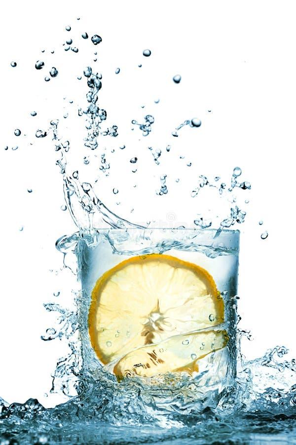 De plons van het water in glas stock afbeelding