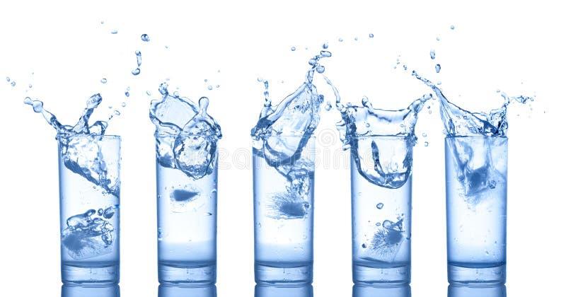 De plons van het water in glazen op wit stock foto