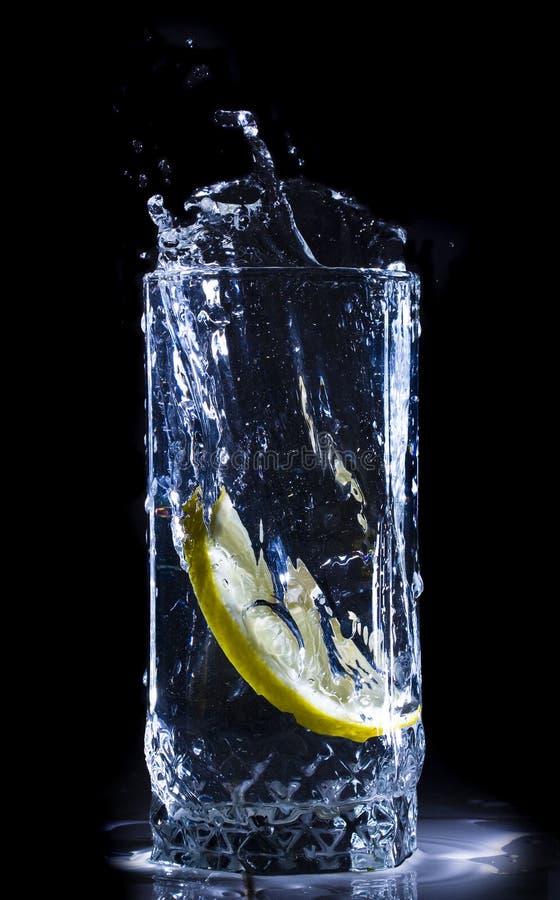 De plons van het water met citroen stock foto's