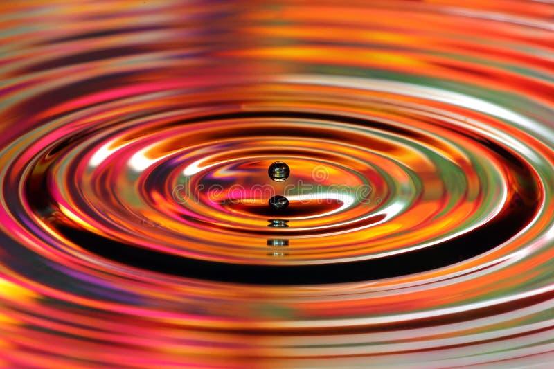 De plons van waterdalingen Rode en gele gekleurde rimpelingen, bezinningen royalty-vrije stock foto