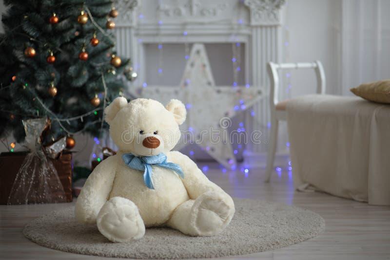 De pluche draagt op een licht tapijt op de achtergrond van een Kerstboom royalty-vrije stock foto's