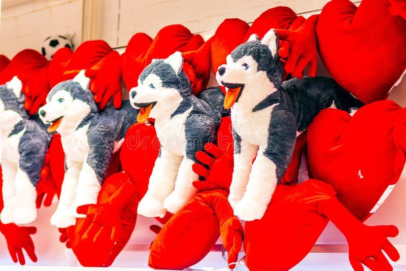 de pluchehonden worden verkocht met plucheharten voor de Dag van Valentine in een grote supermarkt stock fotografie