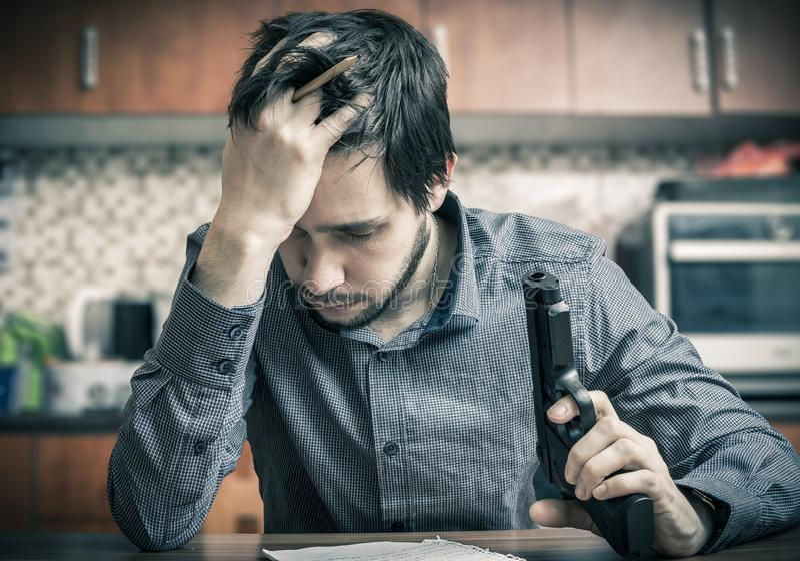 De poging van de zelfmoord De droevige mens met in hand pistool schrijft bericht royalty-vrije stock foto