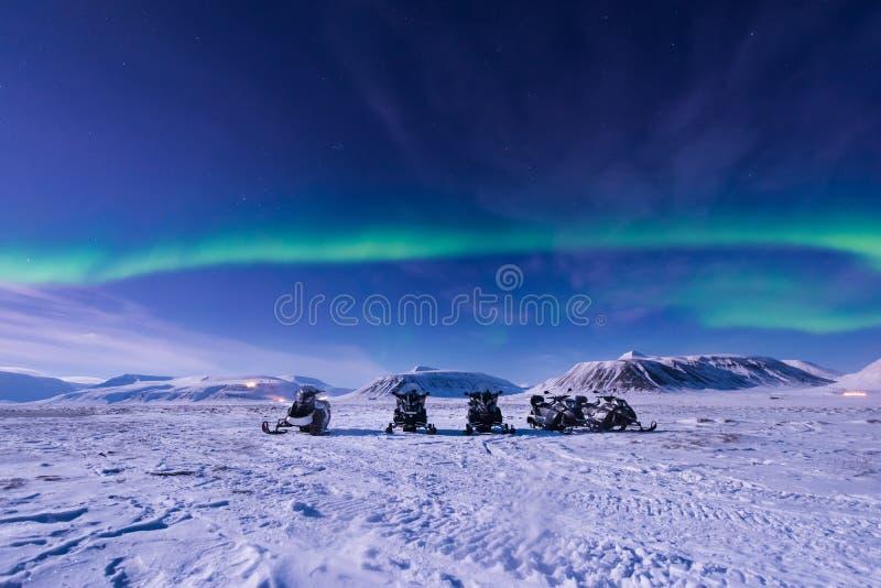 De polaire noordpoolster van de het aurora borealishemel van sneeuwscooter Noordelijke lichten in Noorwegen Svalbard in Longyearb royalty-vrije stock afbeelding