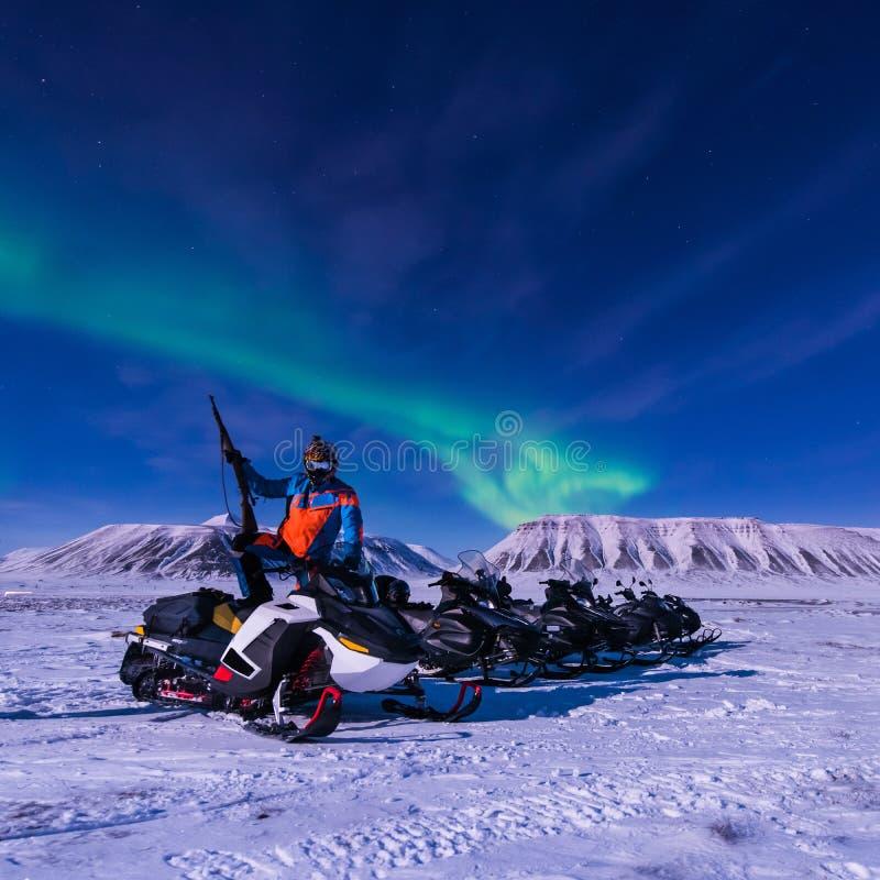 De polaire noordpoolster van de het aurora borealishemel van sneeuwscooter Noordelijke lichten in Noorwegen Svalbard in Longyearb royalty-vrije stock foto's