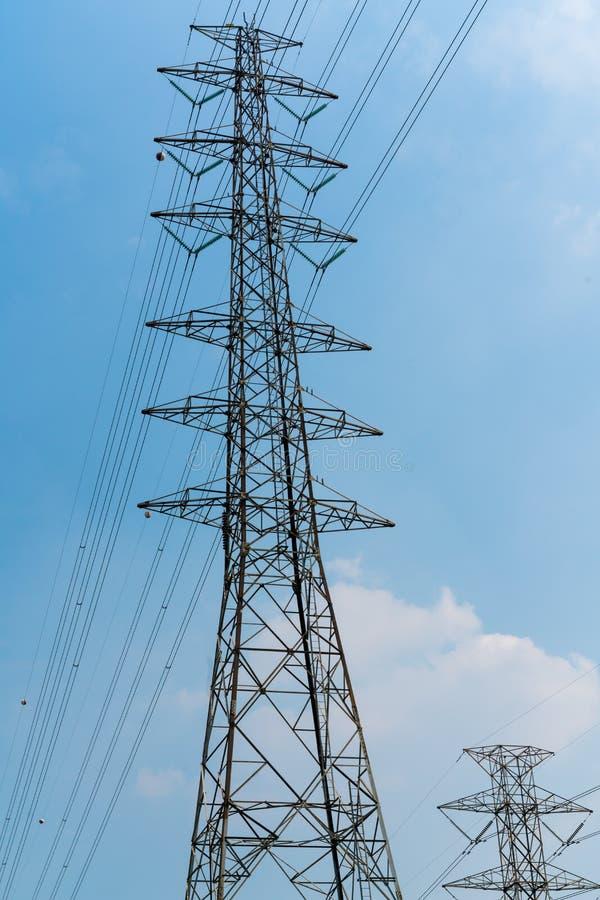 De polen van de hoogspanningsmacht met elektrische draad tegen duidelijk blauw s stock foto's