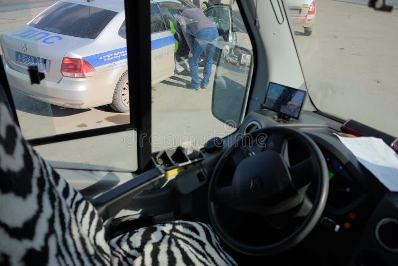 De politie controleert de documenten met de buschauffeur stock foto's