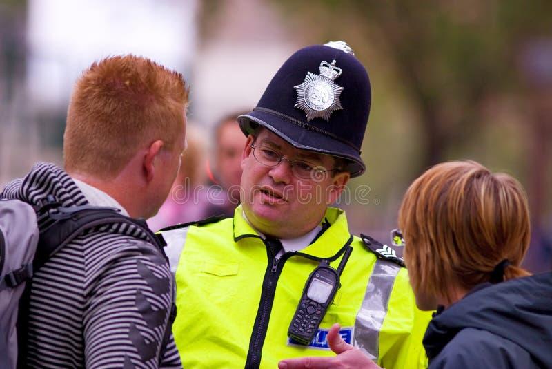 De politieagent adviseert de mensen stock foto