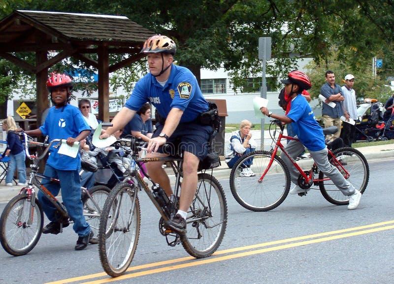 De politieagent op fietspatrouille wordt aangesloten bij in het patroling door jonge geitjes op fietsen stock fotografie