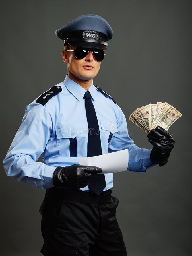De politieagent toont geld en document stock foto