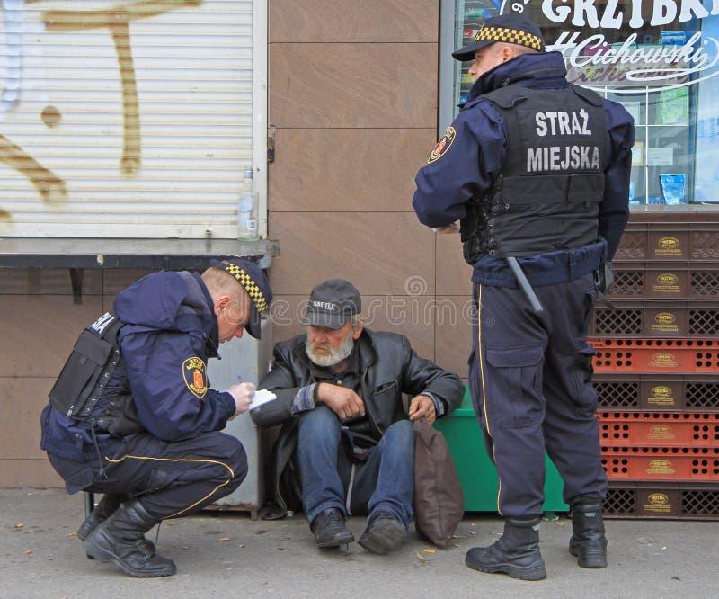 De politiemannen controleren de één of andere vreemde mens stock afbeelding