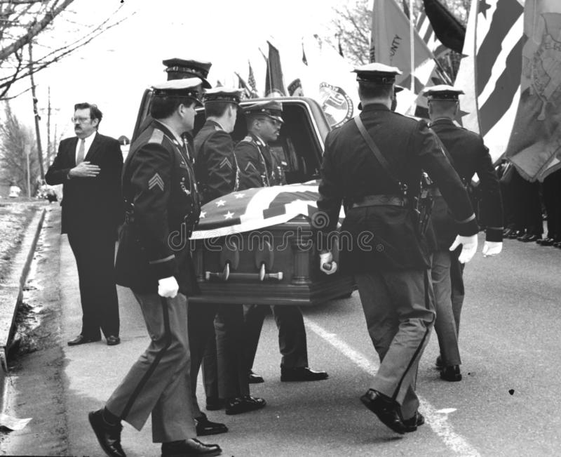 De politiemannen dragen doodskist aan een het wachten lijkwagen bij een begrafenis voor een politieagent gedood in lijn van dutya stock foto