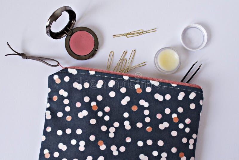 De polka stippelde de zak van de meisjesmake-up, gouden haarspelden, lippenpommade en roze rouge royalty-vrije stock fotografie