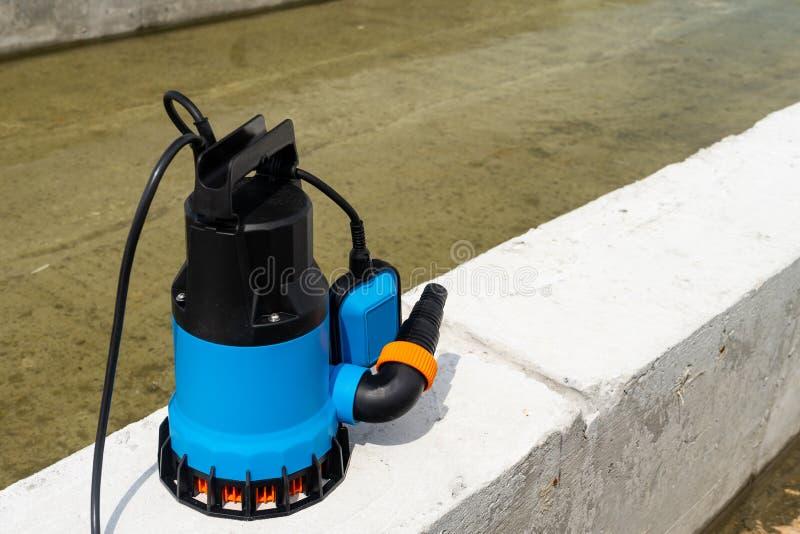 De pomp met duikvermogen ontwatert bouwwerf, diep goed zingt het pompende vloedwater stock foto's