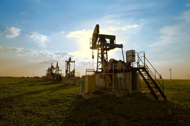 De pomp van de olie bij zonsondergang royalty-vrije stock afbeeldingen