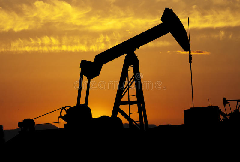 De pomp van de olie bij zonsondergang royalty-vrije stock foto