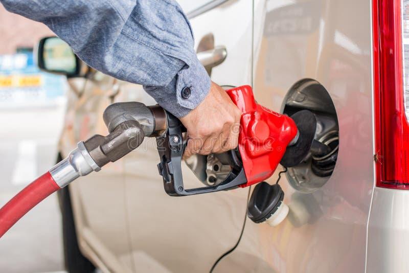 De pompende benzine van de mensenhand met insect op autolichten royalty-vrije stock afbeelding