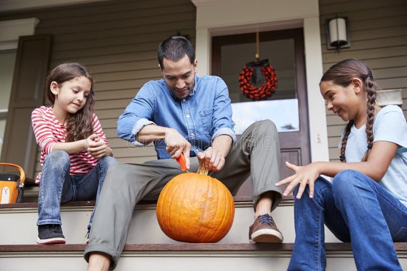 De Pompoen van vaderand daughters carving Halloween op Huisstappen stock foto