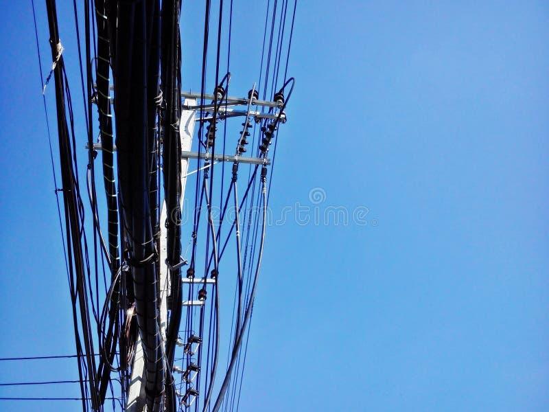 De pool van de hoogspanningsmacht met draden verwarden en de communicatie pool van bodemkant op blauwe hemelachtergrond stock afbeeldingen
