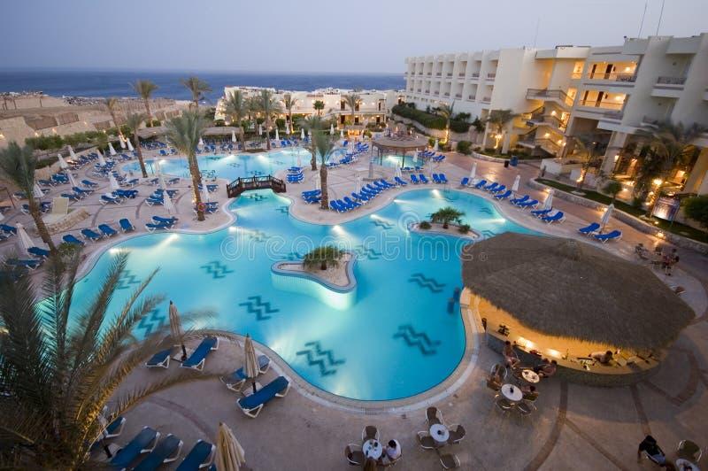 De pool van het hotel bij schemer  stock fotografie