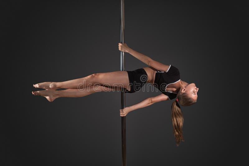 de pooldans van de vrouwenoefening op grijze achtergrond royalty-vrije stock fotografie