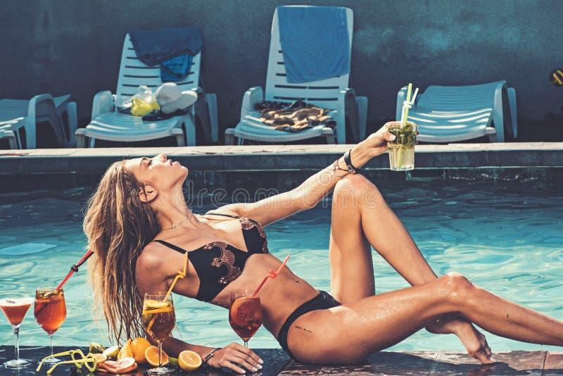 De poolpartij ontspant in kuuroordtoevlucht Cocktail met fruit bij sexy meisje in pool op de Maldiven De maniervrouw met verfrist stock foto