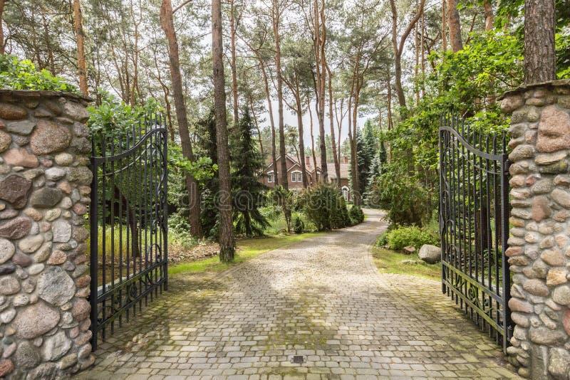 De poort van de ijzeringang en steenachtige weg die tot het huis in het hout leiden royalty-vrije stock fotografie