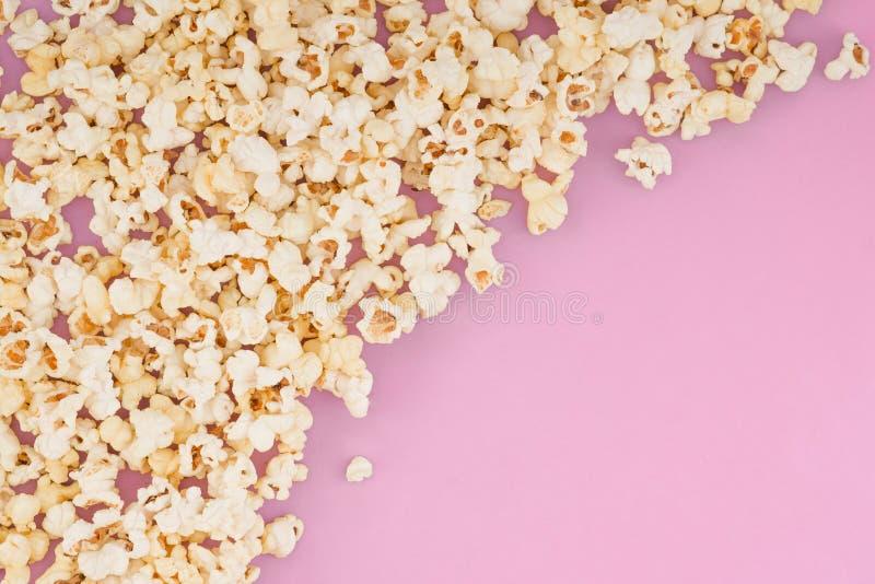 De popcorn verspreidde zich bij de helft van de pastelkleur roze achtergrond en een ruimte voor copyspace Popcorn op een rode ach stock foto's