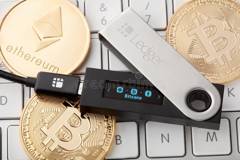 De portefeuille van de grootboekhardware voor cryptocurrency op toetsenbord met gouden muntstukken royalty-vrije stock afbeeldingen
