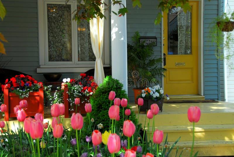 De portiek van het huis met bloemen stock afbeeldingen