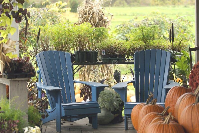 De portiek van het land met blauwe stoelen en pompoenen stock afbeeldingen