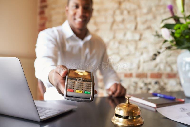 De portier bij hotelontvangst houdt creditcardlezer aan camera stock afbeelding