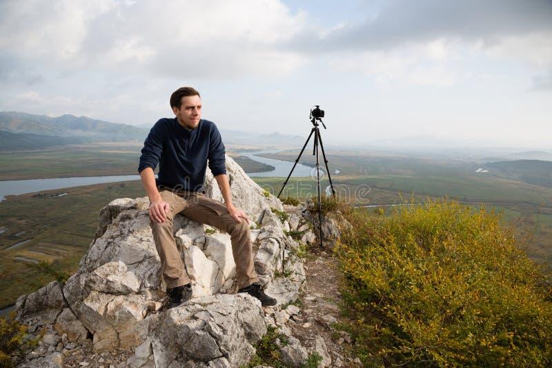 De portretfotograaf zit op een bergtop royalty-vrije stock afbeeldingen