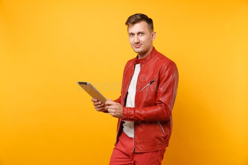 De portretmode die de knappe jonge mens in rood leerjasje glimlachen, t-shirt die het stootkussen van tabletpc gebruiken isoleerd stock fotografie