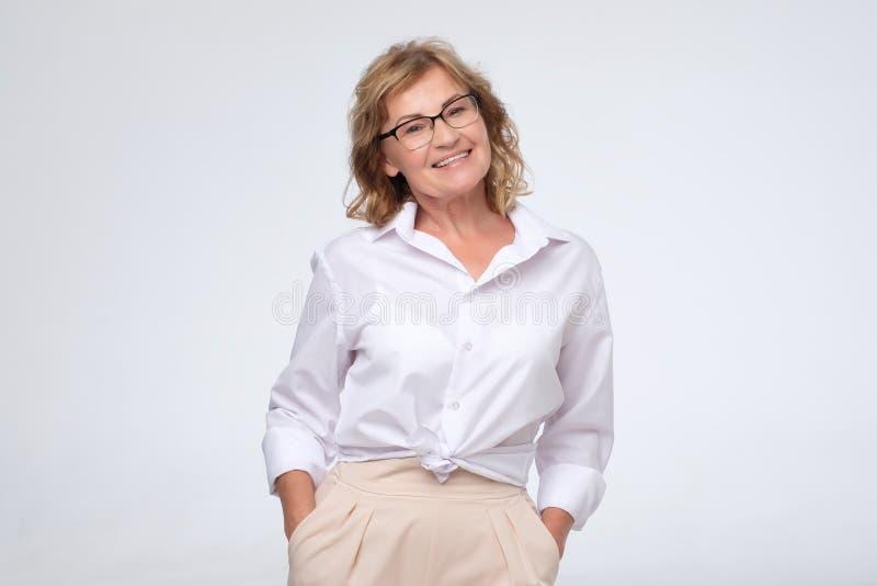 De positieve bedrijfsvrouw van middenleeftijd het stellen over wit met wapens kruiste, exemplaar cpace stock foto
