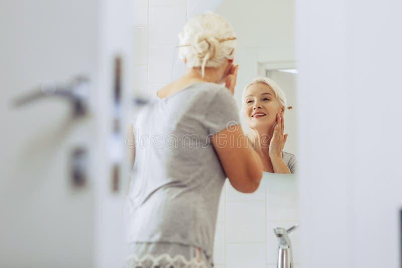 De positieve hogere vrouw van Nice wat betreft haar wang stock foto's