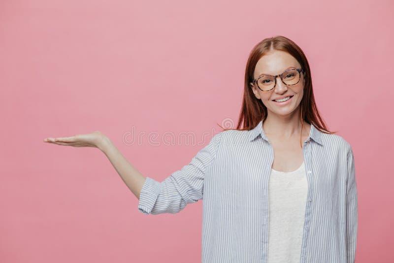 De positieve jonge glimlachende vrouw heft hand op, beweert holding iets, gebaren over exemplaarruimte, gekleed in sylish overmaa stock afbeeldingen