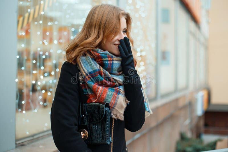 De positieve jonge vrouw in een de winter zwarte laag in modieuze handschoenen met een leerhandtas met een wollen sjaal bevindt z stock fotografie