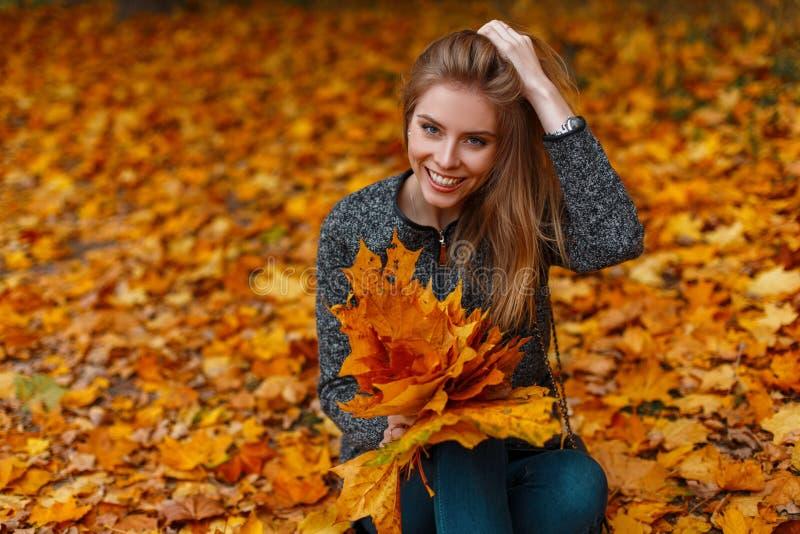 De positieve jonge vrouw met een mooie glimlach in een uitstekende laag in in jeans zit in het park op de achtergrond van gouden stock afbeelding