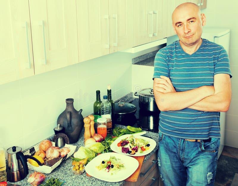 De positieve kereltribunes trots in keukenhanden clasped royalty-vrije stock foto's