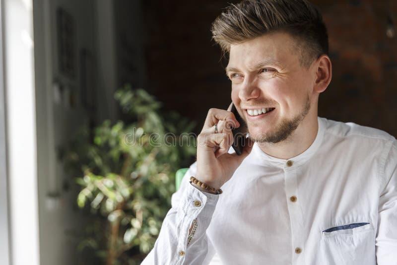 De positieve mens zit en spreekt op de telefoon Hij bekijkt venster De kerel glimlacht Hij is gelukkig royalty-vrije stock afbeeldingen