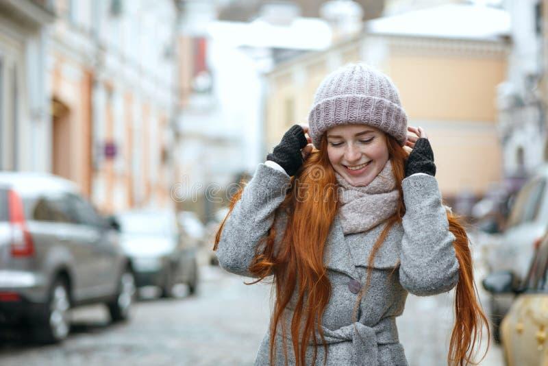 De positieve rode haired vrouw die warme de winterkleren dragen die lopen stock afbeelding