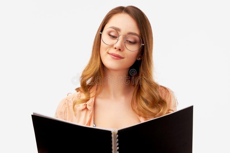 De positieve student treft voor scinetific onderzoek voorbereidingen, bestudeert literatuur Het vrolijke schoolmeisje houdt handb royalty-vrije stock foto's