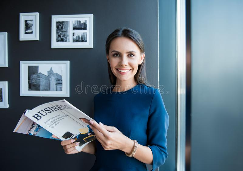De positieve succesvolle jonge dame geniet van lezing stock afbeeldingen