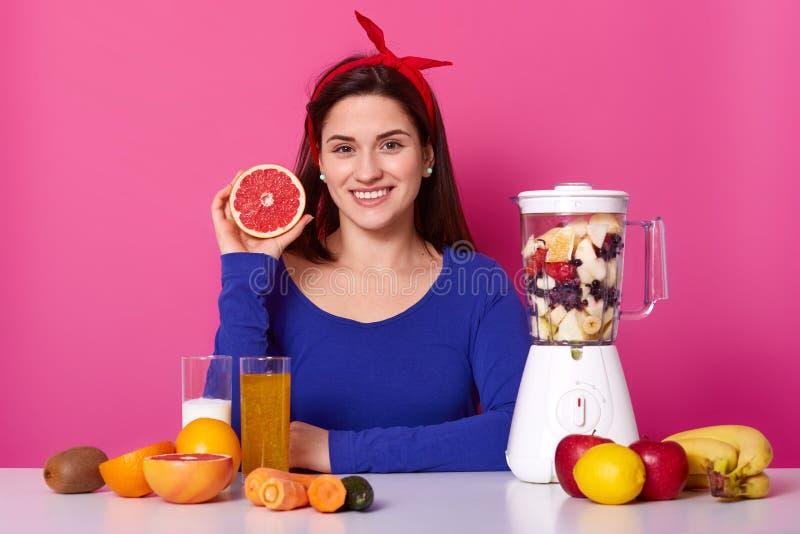 De positieve vrouw in blauwe verbindingsdraad en hoofdband, bereidt gezond sap voor, gebruikt verse ingrediënten, toevoegt besnoe royalty-vrije stock foto's