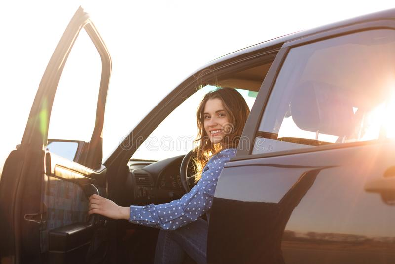 De positieve vrouw zit in zwarte auto, kijkt met gelukkige glimlach op gezicht, probeert om deur te sluiten, klaar voor lange rei royalty-vrije stock foto