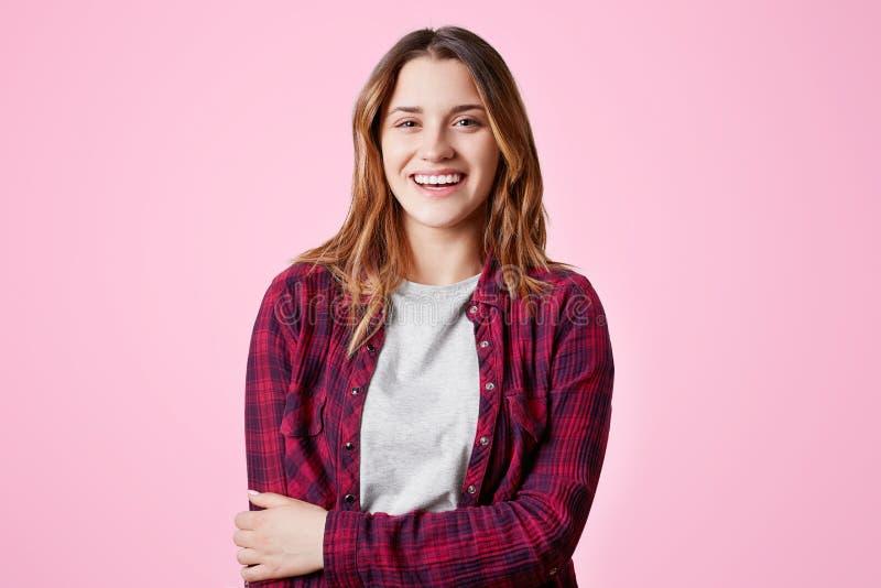 De positieve vrouwelijke student verheugt zich om vakantie, gelukkig gekleed in geruit modieus overhemd, glimlachen te hebben die royalty-vrije stock afbeeldingen