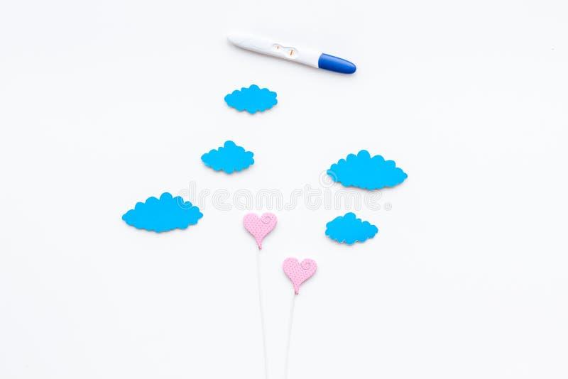 De positieve zwangerschapstest dichtbij stuk speelgoed wolken en het hart ondertekenen op de witte ruimte van het achtergrond hoo stock foto's